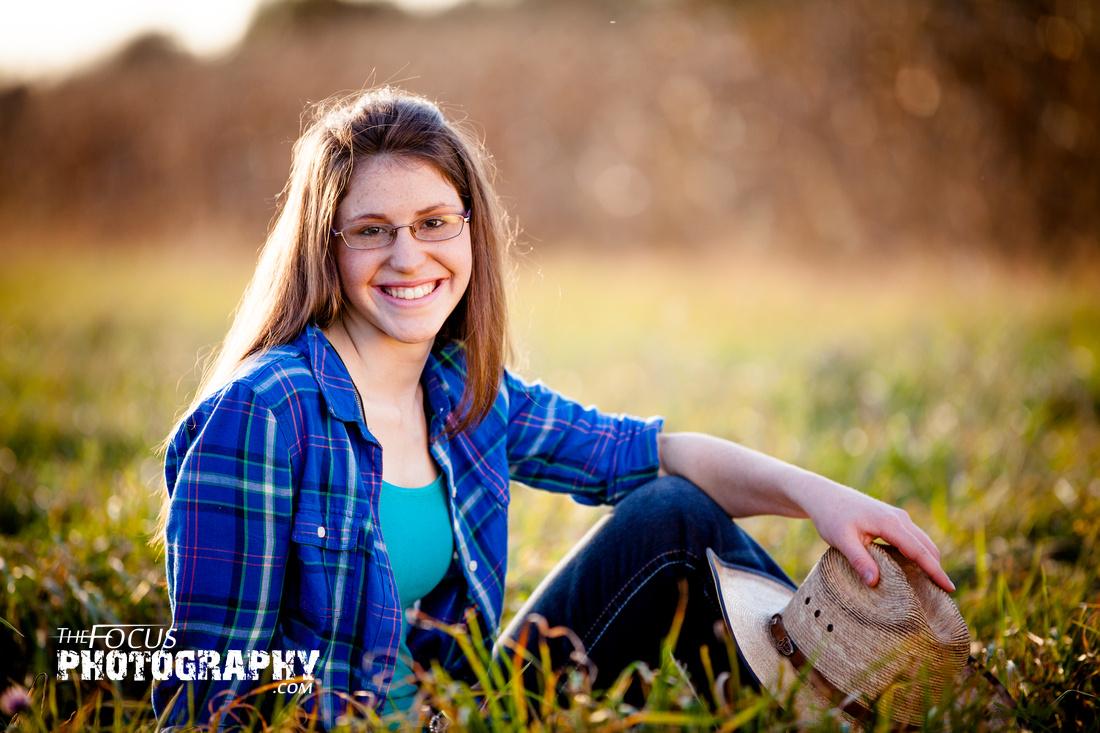 Senior portrait cowgirl in field