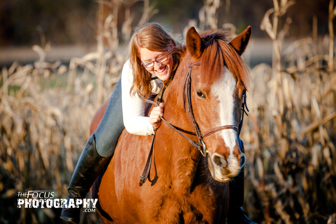 girl riding her horse in a corn field