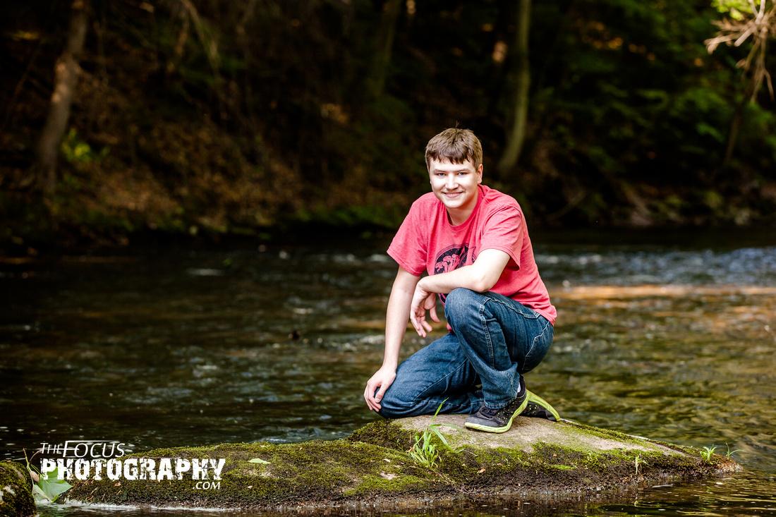 boy senior portraits in the woods near creek