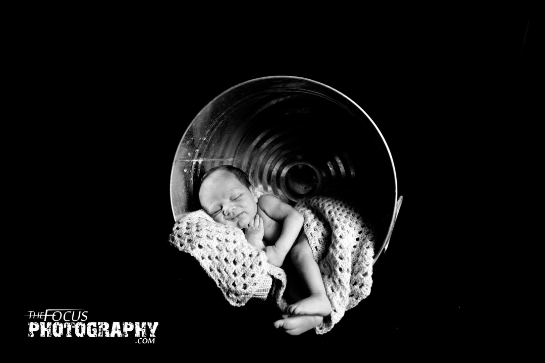 Newborn baby in tin bucket