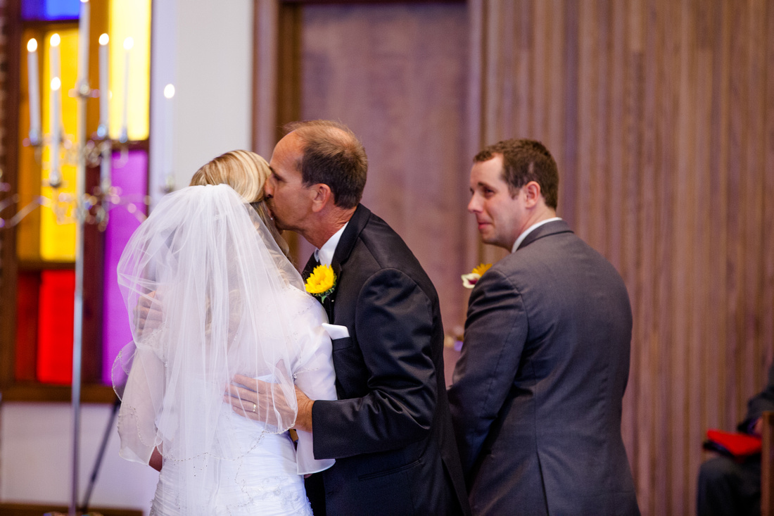 father of the bride kisses her before giving her away